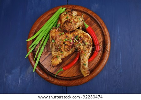 meat : grilled quarter chicken garnished with green onion pens and red peppers on wooden plate over blue wooden background