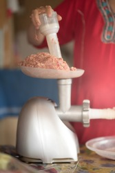Meat grinder with fresh forcemeat and woman making sausages in kitchen