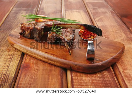 meat on wooden plate : roast ribs on wood with tomatoes chives and dry spices over wooden table - stock photo