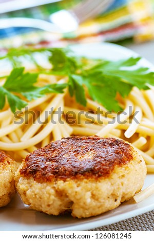 Meat patties and pasta with parsley in bowl on table.