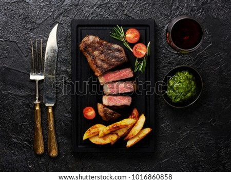 Meat Picanha steak, traditional Brazilian cut with potato wedges, chimichurri sauce and rosemary.