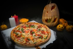 meat pizza on takeaway box near Halloween decoration. Scary pumpkins with painted faces, Lights of burning candles In horror smoke. Dark background with cobwebs and spiders near fast food