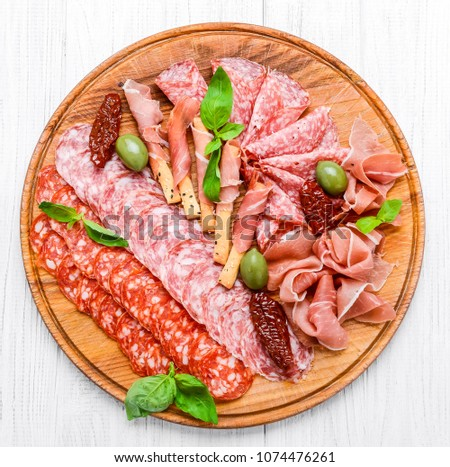 Meat plate with salami sausage, chorizo, parma on a wooden background