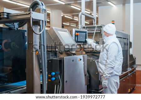 Meat processing plant. Production line of meat.Line for the production of meat with packaging and cutting . Industrial equipment at a meat factory.