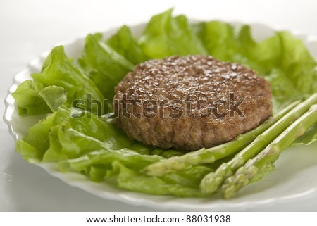 Meat rissole with lettuce and asparagus on the white plate