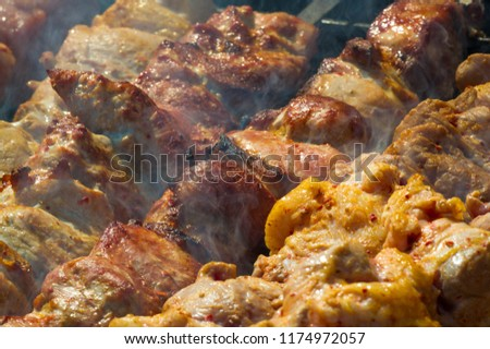 Meat roasted on coals on a spindle, barbecue, shish kebab. a dish of marinated meat and vegetables. #1174972057