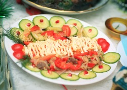 meat salad with pomegranate seeds at the Christmas table