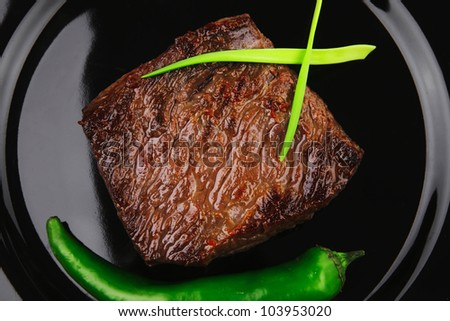 meat savory : grilled beef fillet mignon on black plate with pepper and chives isolated over white background - stock photo