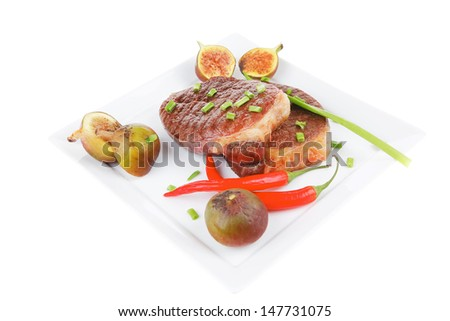 meat savory : grilled beefsteak served with hot cayenne peppers green chives and sweet figs on plate isolated over white background