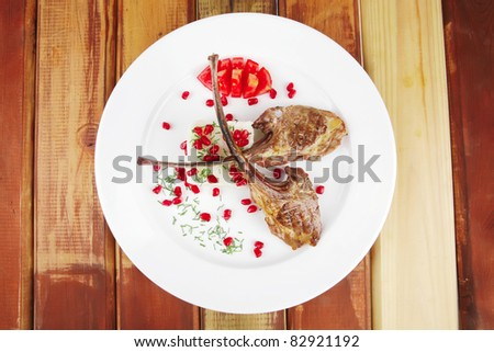 meat savory: roast veal ribs with rice garnish and pomegranate seeds on white over wood