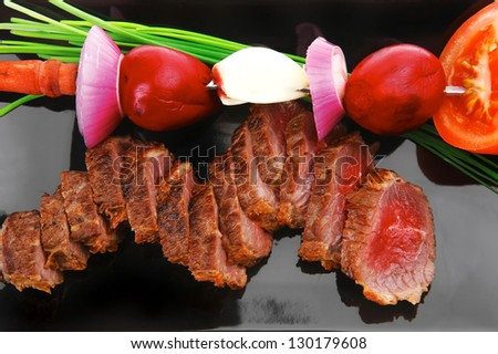 meat savory : roasted bbq meat served on black plate with vegetables on spit isolated on white background