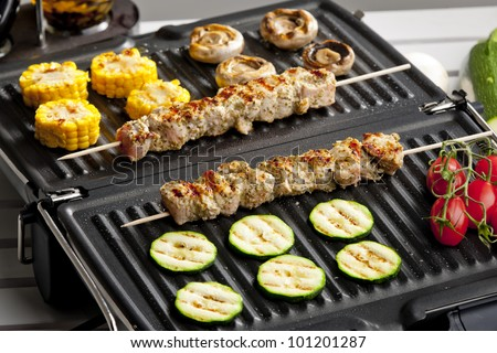 meat skewers and vegetables on electric grill