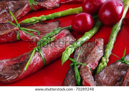 meat slices and asparagus on red over white closeup . shallow dof