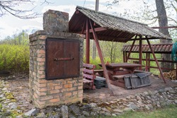 Meat smoker in the bbq area of the Mikko farm's garden. Wooden construction as the roof for the dining area. Smoker made out of red bricks. Mikko farm's award winning garden. Estonia, Polvamaa