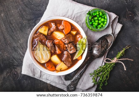 Meat stew with beef, potato, carrot, onion, spices, green peas. Slow cooked meat stew, bowl, wooden background. Hot autumn/winter dish. Closeup. Top view. Comfort food. Homemade soup/ragout/casserole