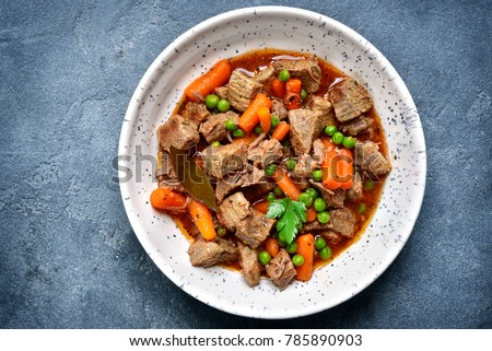 Meat stew with carrot and green pea in a white bowl over dark grey slate or stone background.Top view. Foto stock ©