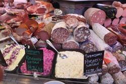 Meat store in Gothenburg Market Hall (Saluhallen), Sweden. Various smoked hams, bacons, sausages, salami and salads.