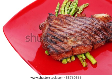 meat table : grilled beef fillet with asparagus served on red dish isolated over white