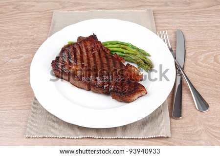 meat table : grilled beef fillet with asparagus served on white plate with cutlery over wooden table