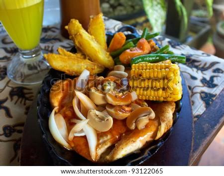 meat with fried potatoes and garnish: champignon mushroom, carrot,corn