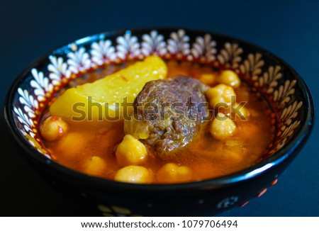 Meat with potatoes, chickpeas and red sauce. Azeri food Bozbash isolated on black background