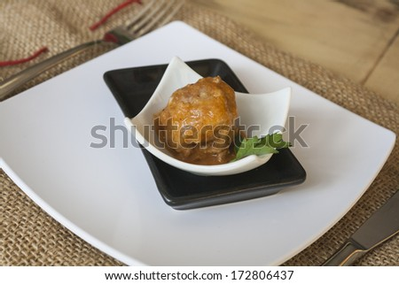 Meatball of minced meat with parsley on small plates in black and white