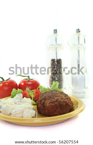 Meatball with potato salad, fresh lettuce and tomato pieces - stock photo