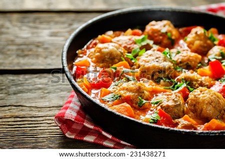 meatballs baked with vegetables on a dark wood background. tinting. selective focus