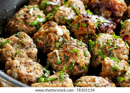 Meatballs cooking in a pan, with parsley scattered on top.  Delicious!