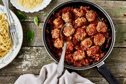 Meatballs in tomato sauce in a frying pan and spaghetti on a wooden rustic table. Delicious lunch, top view