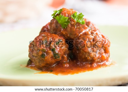 Meatballs in tomato sauce on a green plate.