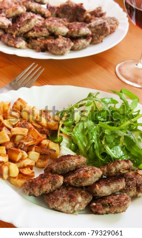 Meatballs with beef and spices, fries potatoes and salad