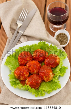 meatballs with tomato sauce on lettuce and glass of wine