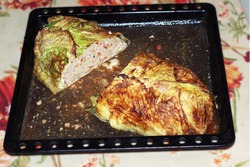 meatloaf in Savoy cabbage leaves, oven-baked in baking tray full of its own juice. piece is cut out of the middle, texture of dense baked minced meat with vegetables is visible on the cut