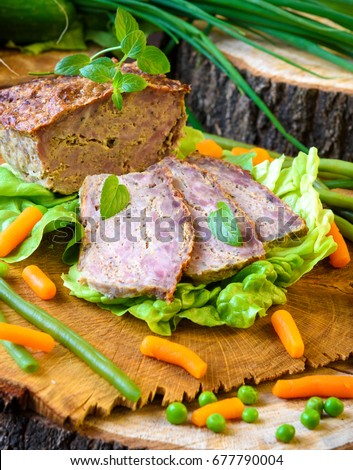 Meatloaf with peas, carrot, lettuce and herbs on a wooden board Zdjęcia stock ©