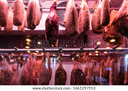 Meats preserving inside refrigerator. Large cold cuts of meat are seen hanging inside a fridge, salted joints chilled and curing ready to be sold by a delicatessen for consumption.