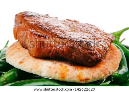 meaty food : grilled meat steak on arabic pita over green hot chili peppers on a white back