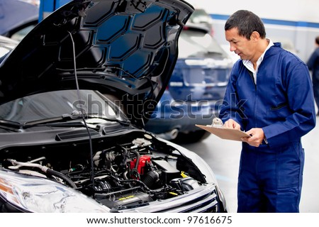 Mechachic checking on a car engine and taking notes - stock photo