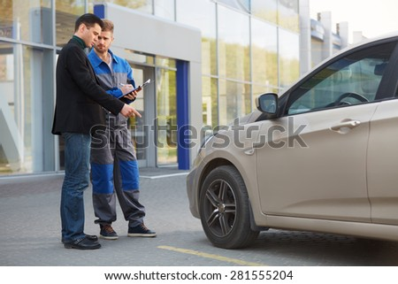 Mechanic and Customer Discussing Problem With Car. Auto Repair Shop