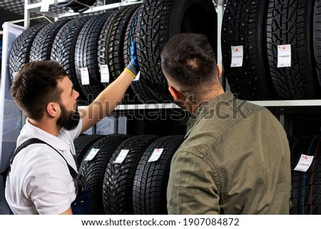 mechanic and customer talking about tire at the repair garage, replacement of winter and summer tires. seasonal tire replacement concept. client is choosing the best one for his auto