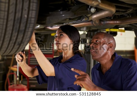 Mechanic And Female Trainee Working Underneath Car Together #531128845