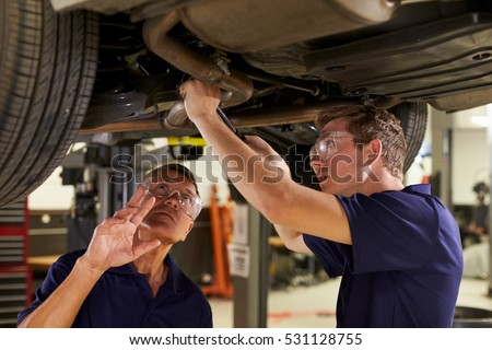 Mechanic And Male Trainee Working Underneath Car Together #531128755