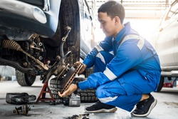 Mechanic Asian man fixing repairing car rotor spindle hub wheel automobile vehicle parts examining using tools equipment working hard in workshop garage support and service in overall work uniform