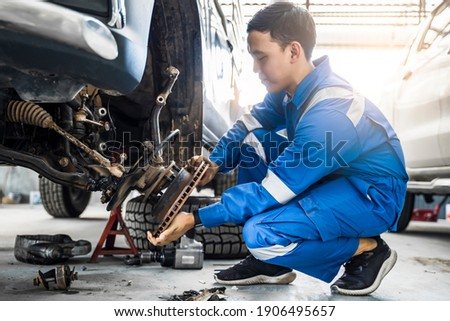 Mechanic Asian man fixing repairing car rotor spindle hub wheel automobile vehicle parts examining using tools equipment working hard in workshop garage support and service in overall work uniform Foto d'archivio ©