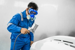 Mechanic Asian man spray painting airbrush pulverizer car body in paint chamber repairing car automobile vehicle parts using tools equipment in workshop garage support service in overall work uniform