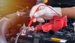 Mechanic car service using Multimeter to check the voltage level in a car battery- Car maintenance.