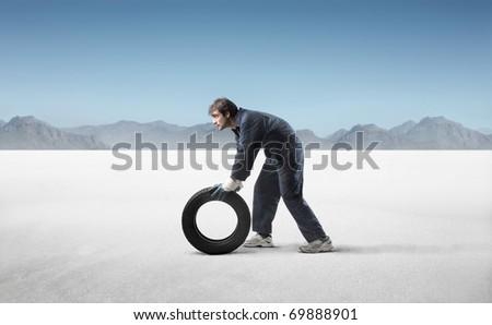 Mechanic carrying a tyre in a desert