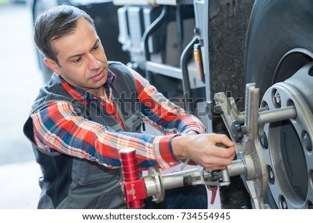 mechanic changing car tire with wheel wrench #734554945