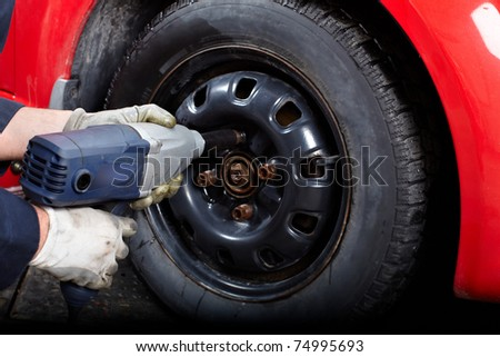 Mechanic changing wheel on car with impact wrench.