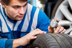 Mechanic, checking a measurement gauge to check the depth of a tread on a car tire for wear, to make sure it is still within regulations and safe to use. Focus on the hands and the gauge